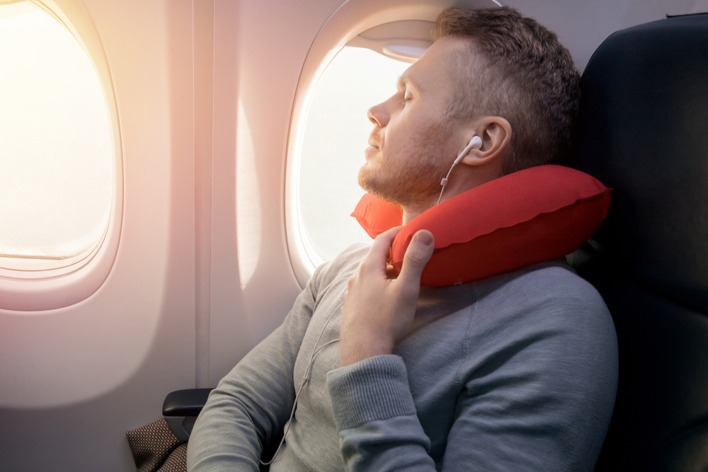 Man using neck pillow on airplane