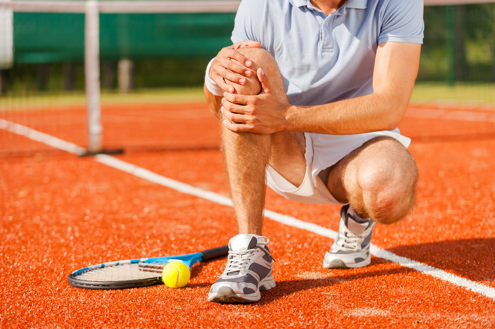 Man on tennis court holding his knee