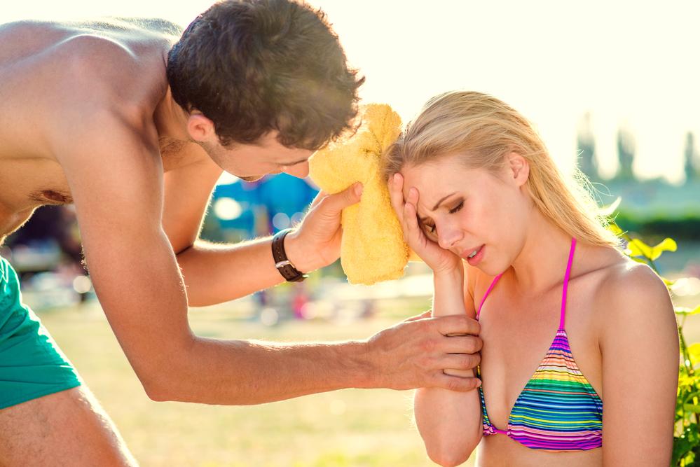 Woman on beach suffering heatstroke