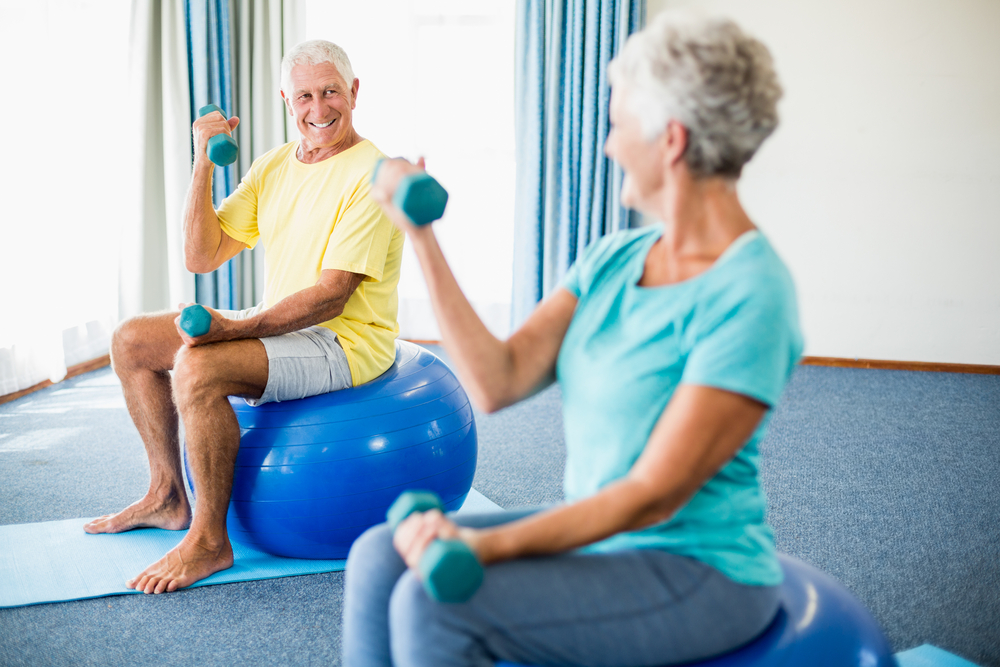 Senior couple on exercise balls with weights