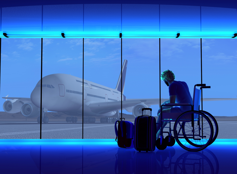 Man in wheelchair with luggage looking out at plane
