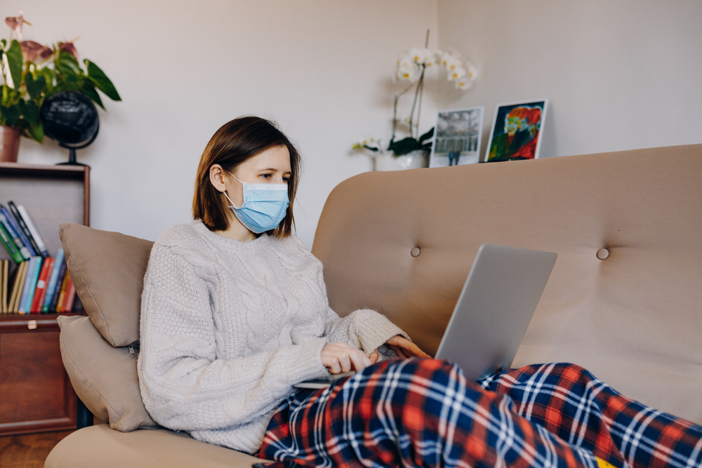 Woman wearing face mask using laptop on couch