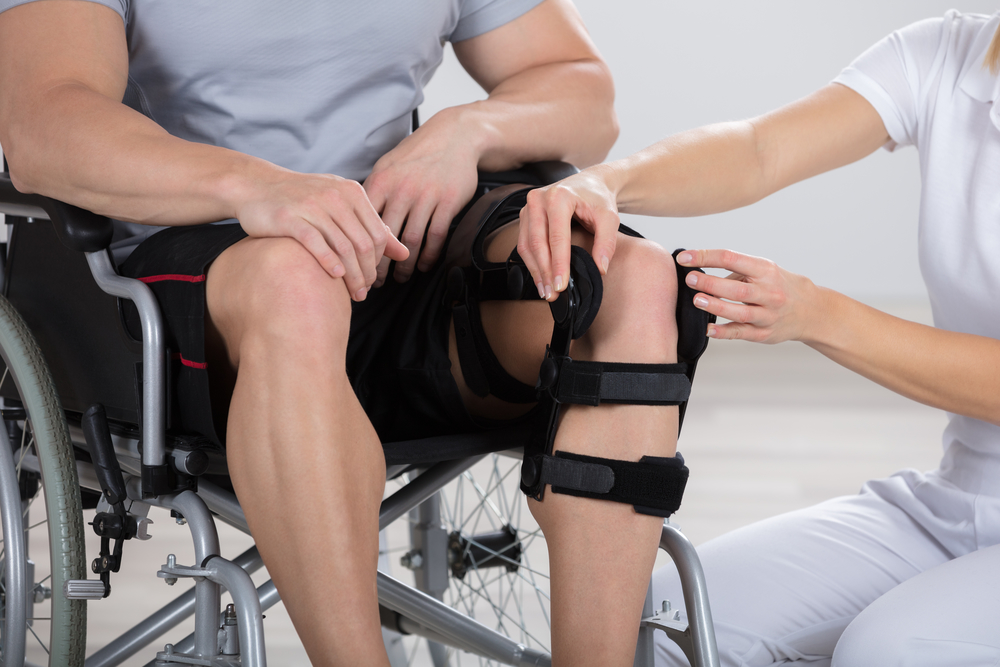A nurse assisting a man in a wheelchair with his knee brace.