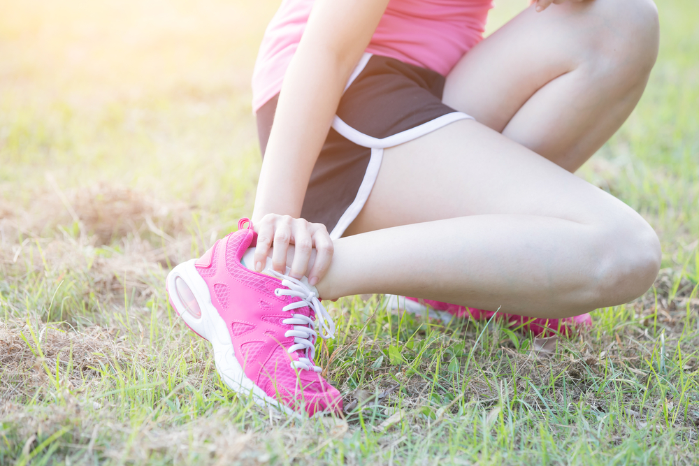 Woman in pink running shoes holding injured ankle