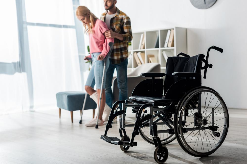 Woman using crutches near wheelchair