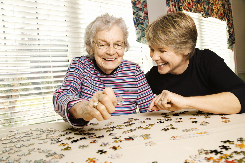 Young woman and elderly woman doing puzzle together