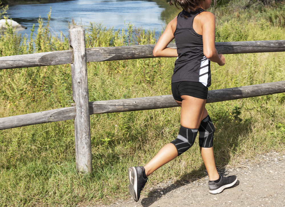 Woman running outdoors with knee support braces