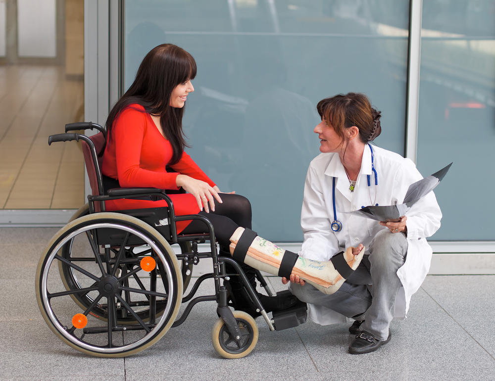 Woman sitting in a wheelchair with a cast on her leg while talking to a squatting doctor.