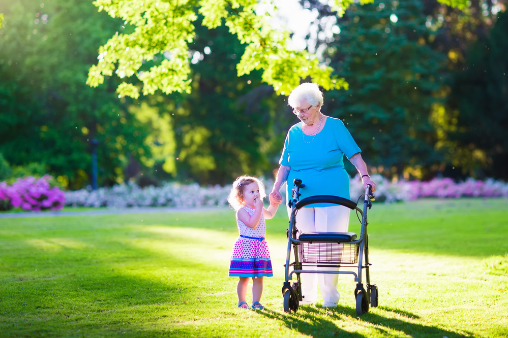 Elderly woman using a walker to stroll with a young girl outside.