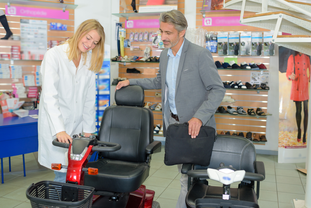 Woman with a white coat looking at an electric wheelchair with a man in a suit.