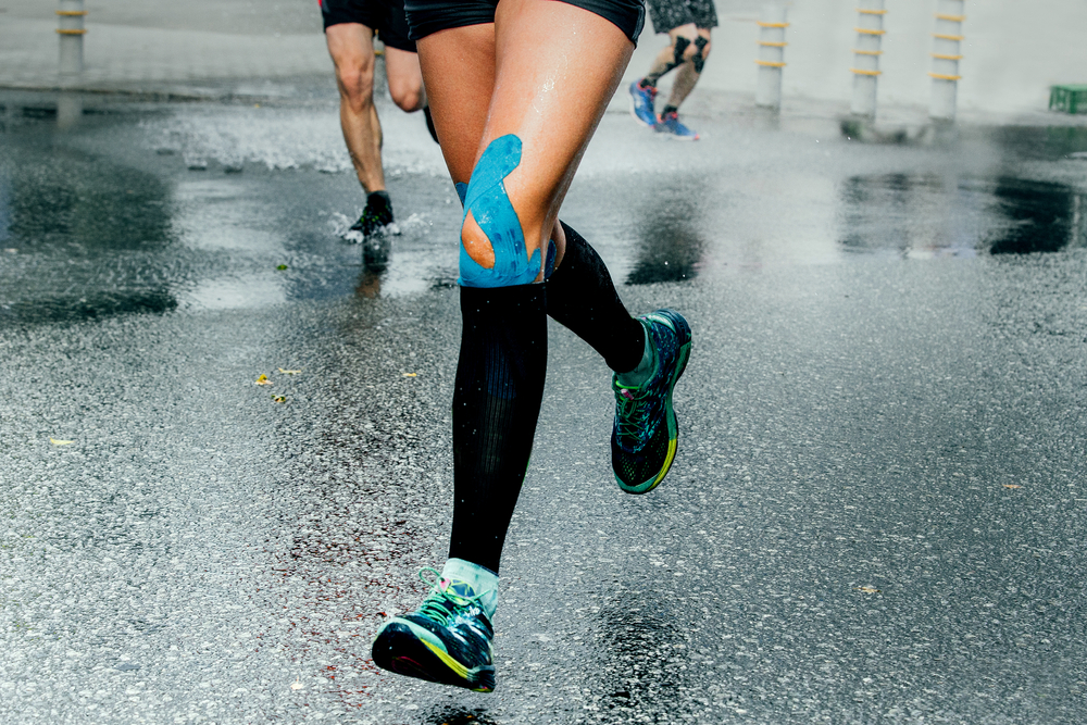 Feet of female runner wearing compression socks and athletic tape