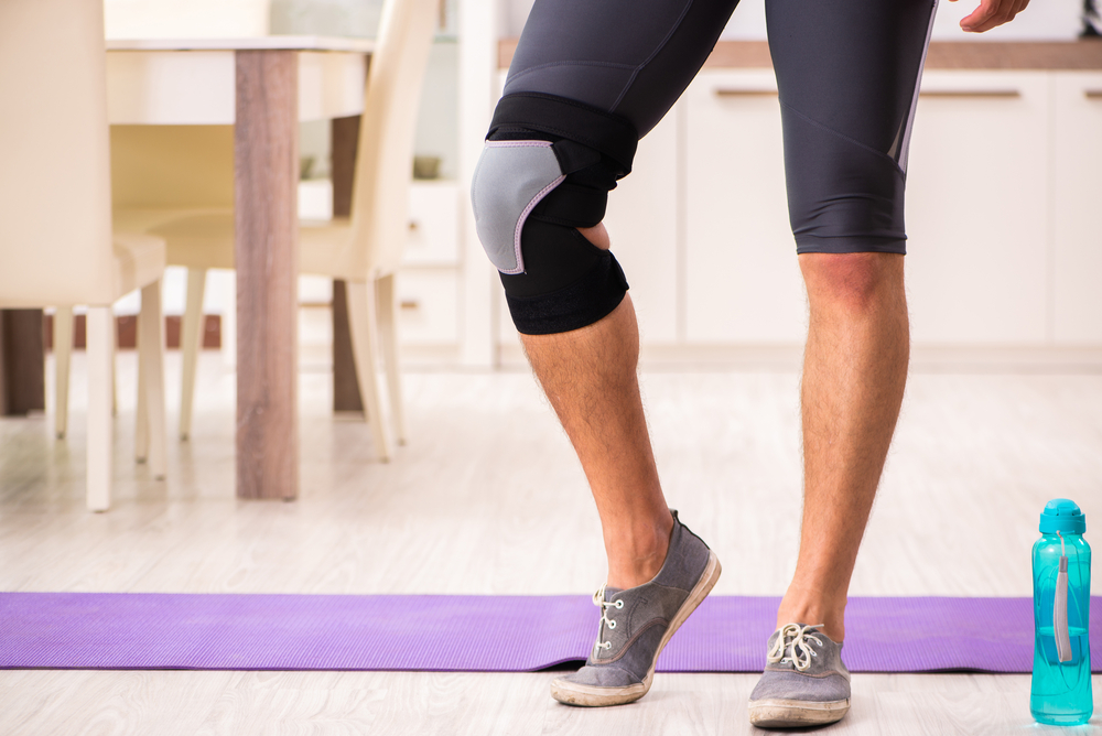 Legs with knee brace standing near yoga mat